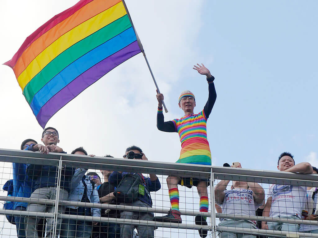 Participants on the pedestrian bridge waved rainbow flags.